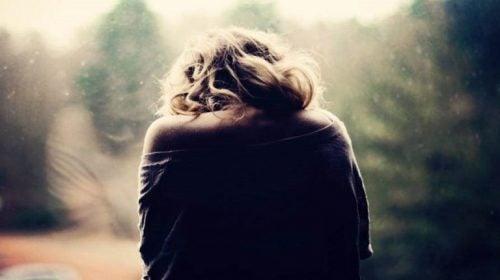 Kvinde ved vindue føler fortvivlelse