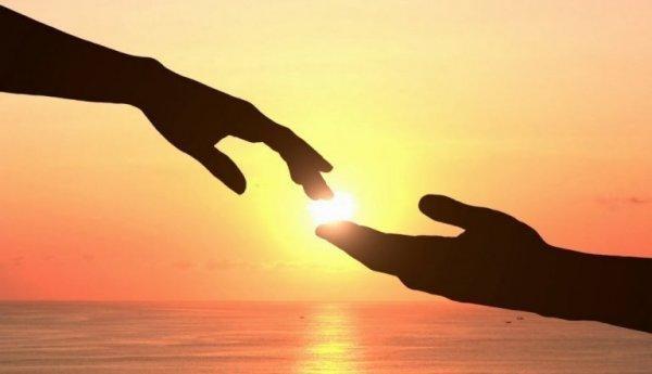 To hænder mødes foran solen