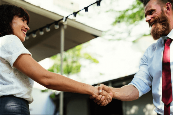To ansatte giver hånd og smiler