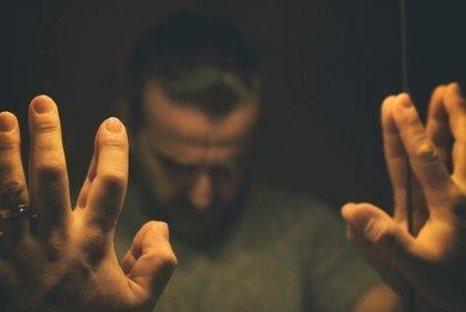 Mand sætter hænder på spejl i illusionen om gennemsigtighed