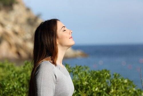 Smilende kvinde oplever velvære i solen