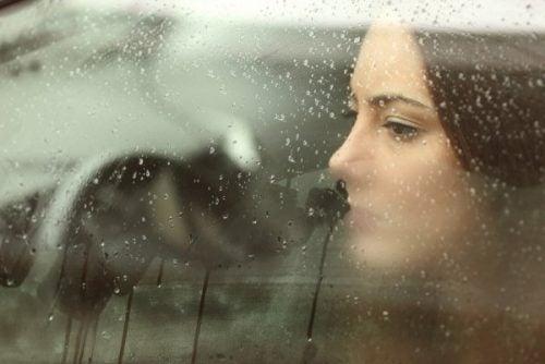 Kvinde kigger ud af vindue med regn på