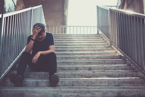 Mand på trappe tager sig til hoved