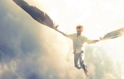 Dreng svæver med fjer som vinger