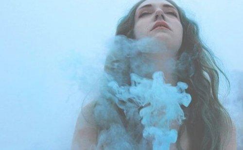 Kvinde med lukkede øjne og røg omkring hals