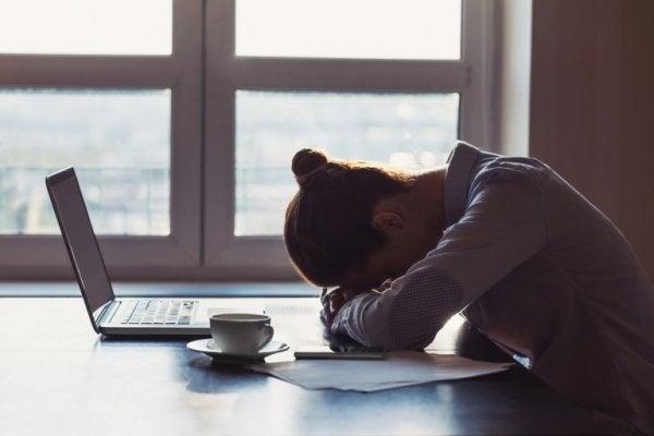 En trist kvinde med hovedet på et skrivebord