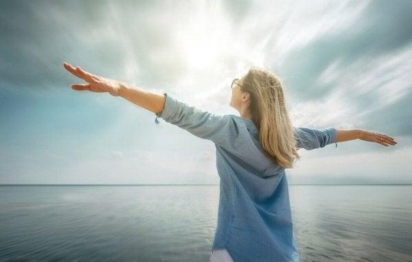En glad og afslappet kvinde med armene ud til siderne ved havet