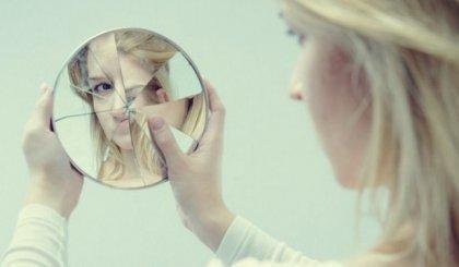 Kvinde ser sig selv i smadret spejl