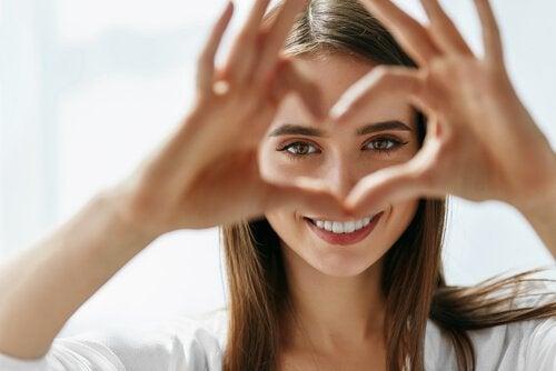 En kvinde laver et hjerte med fingrene