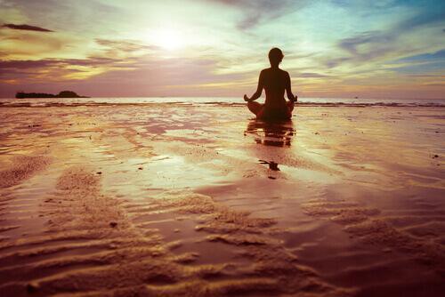 kvinde mediterer på strand