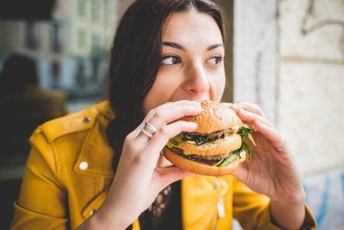 Kvinde spiser en burger, hvilket symboliserer vaner, der sænker din iq