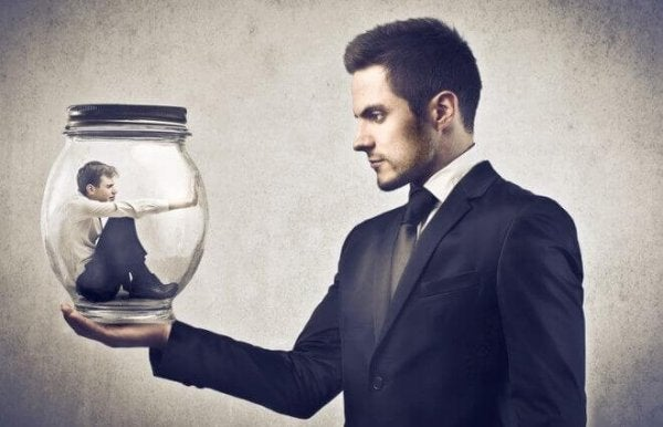 En mand, der holder en flaske med en mand indeni, som repræsenterer for lidt medarbejderbeskyttelse