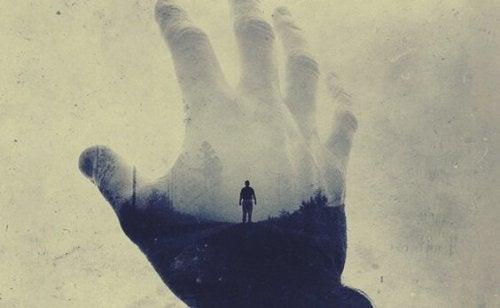 Hånd griber ud efter silhuet af person i forsøg på at behandle angst