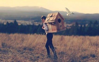 Mand går med stort fuglehus på ryggen