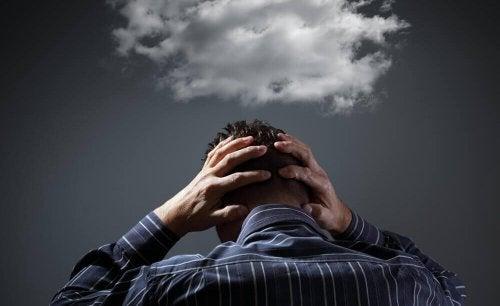 En mand med en sky over hovedet, der symboliserer negative tanker
