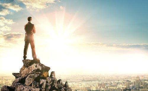 Mand står på toppen af klippe og ser ud på storby