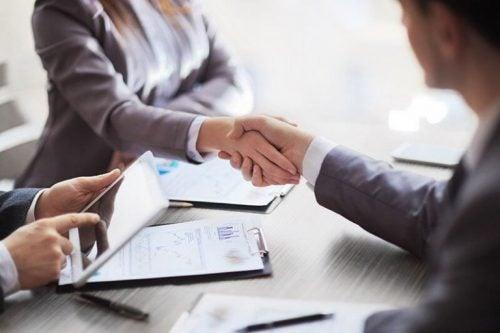 Personer giver hånd til jobsamtale