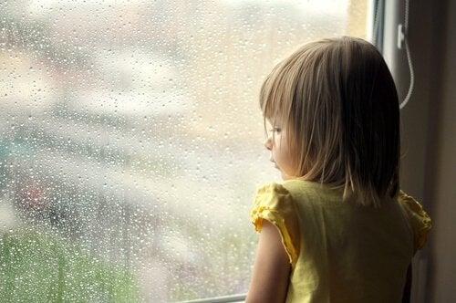 Lille pige ser ud på regn gennem vindue