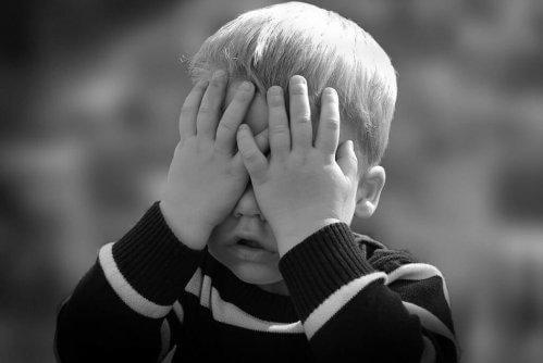 Lille dreng gemmer ansigt bag hænder