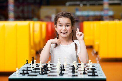En smilende pige spiller skak