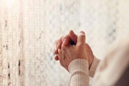 Bedende hænder foran et tæppe