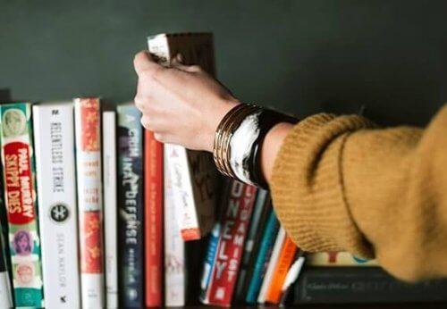 En hånd vælger en bog fra en hylde