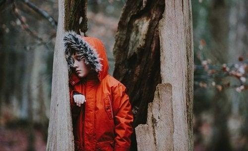 En dreng i udhulet træ i skov