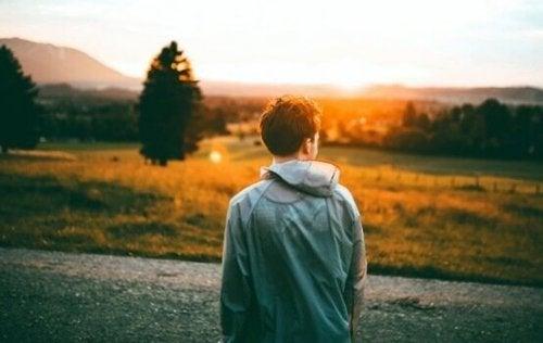 Dreng foran mark ved solopgang