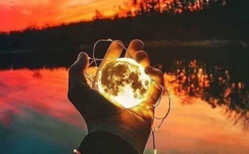 en person holder månen i hånden ved en sø