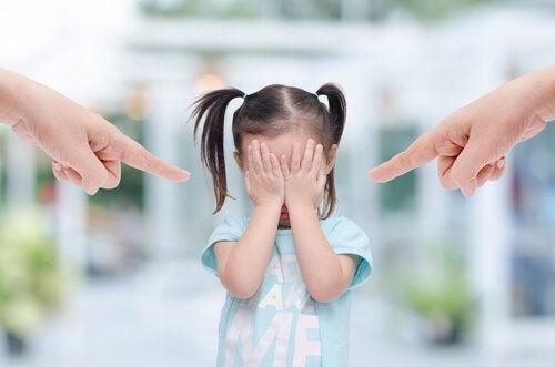 Forældre peger fingre af pige, der skjuler ansigt bag hænder