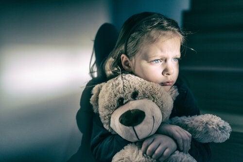 Pige, der krammer et plusdyr og symboliserer omsorgssvigt
