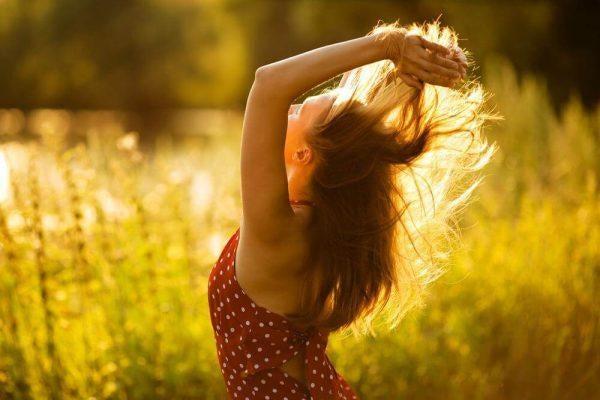 Kvinde på eng leger med sit hår og nyder friheder