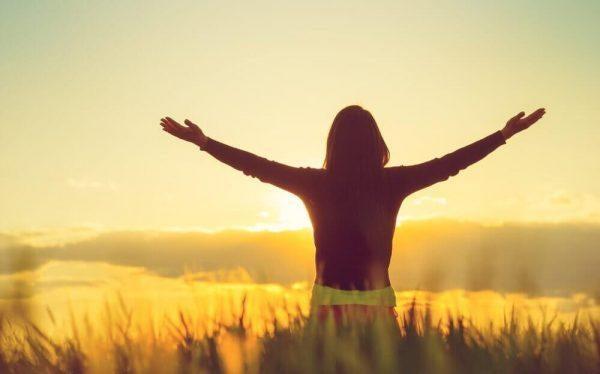 Kvinde med hænderne ud til siderne imødekommer sol på mark