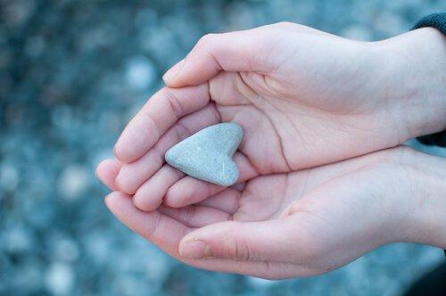 Sten formet som hjerte i hånd