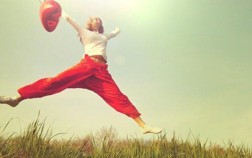 Kvinde hopper med rød ballon