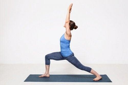 En kvinde udfører krigerstillingen. Den første stilling i yoga for begyndere