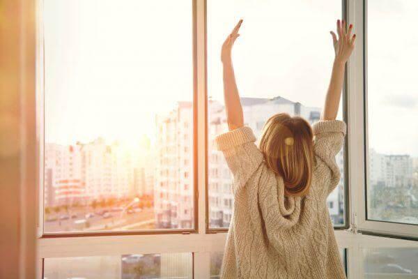 Kvinde med hænderne over hoved er klar til at imødekomme en ny dag