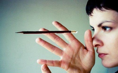 Kvinde fokuserer på blyant foran ansigt