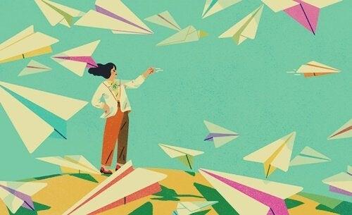 Kvinde flyver med papirsfly på bakke
