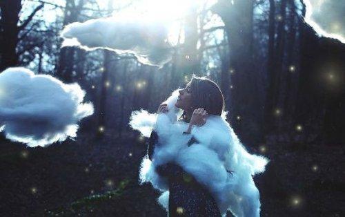 Kvinde omringet af skyer i skov