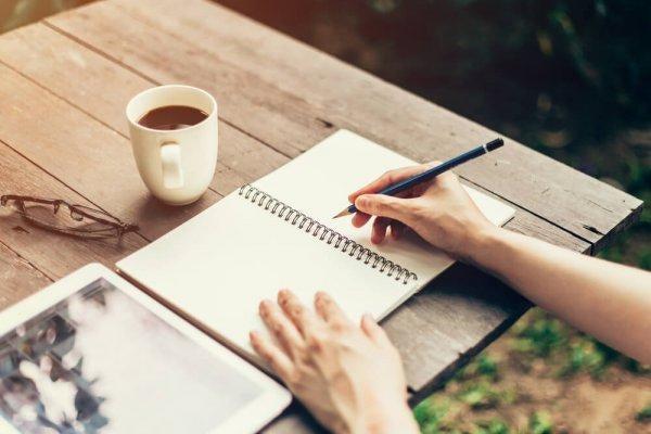 kvinde skriver i notesbog udenfor