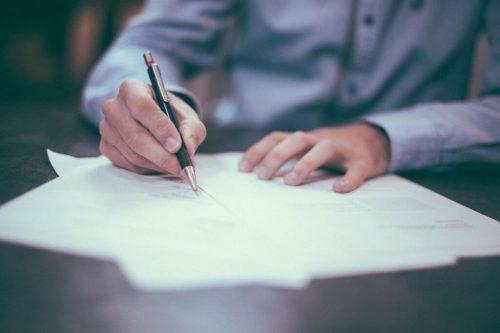 Person skriver ned, hvad trinene er til at opfylde forsæt