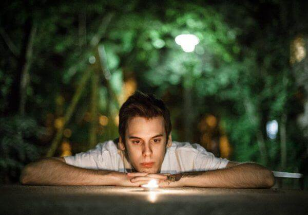 Mand ligger på jord og ser på stearinlys