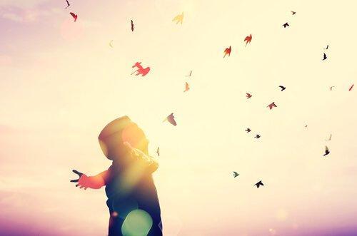 Person spreder arme ud til siderne og tager imod flyvende blade i luften