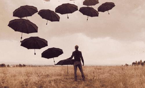 Mand med sorte paraplyer på mark