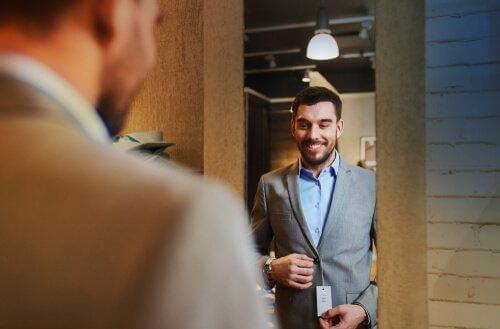Mand i jækkesæt foran spejl illustrerer, at vores tøj sender forskellige signaler