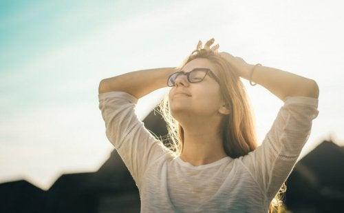 En kvinde med en optimists hjerne smiler til solen