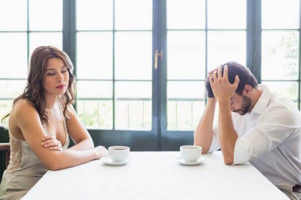 Mand og kvinde er frustrerede ved bord med kaffekopper