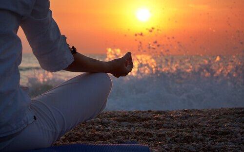 Person på strand mediterer ved solnedgang
