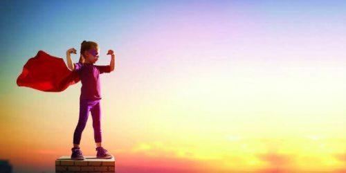 Pige klædt i superheltekostume på toppen af bygning